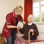 pregnant carer helps her elderly pacient to her feet